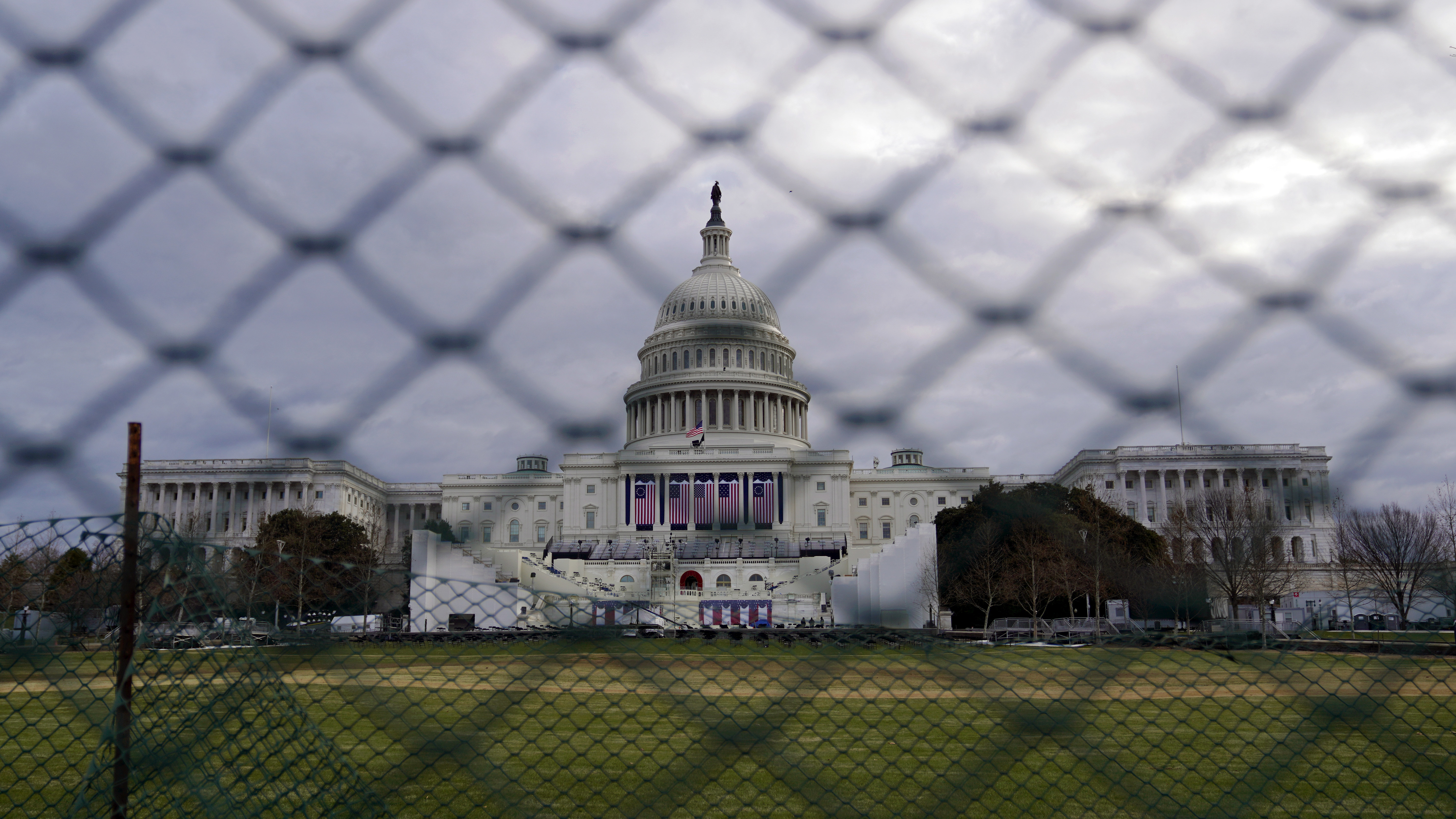 The U.S. Capitol is visible behind fences on Sunday following the Jan. 6 riot by pro-Trump extremists. This week's events will have the largest security presence of any inauguration in U.S. history.