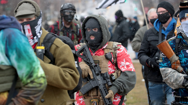 Armed demonstrators protest outside of the Michigan state capital building on Sunday in Lansing, Michigan.