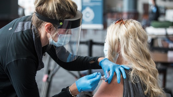 A woman receives the COVID-19 vaccine at Gillette Stadium on Jan. 15, in Foxborough, Mass. Setting up community vaccination centers will be a key to getting the vaccine to millions, an adviser to President Biden says.