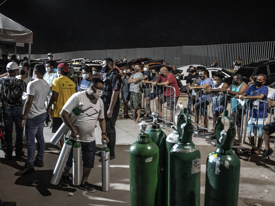 Workers check oxygen tanks at a hospital in Manaus, Brazil. Severe oxygen shortages as a second coronavirus wave is surging have prompted local authorities to airlift patients to other parts of Brazil. (Jonne Roriz/Bloomberg via Getty Images)