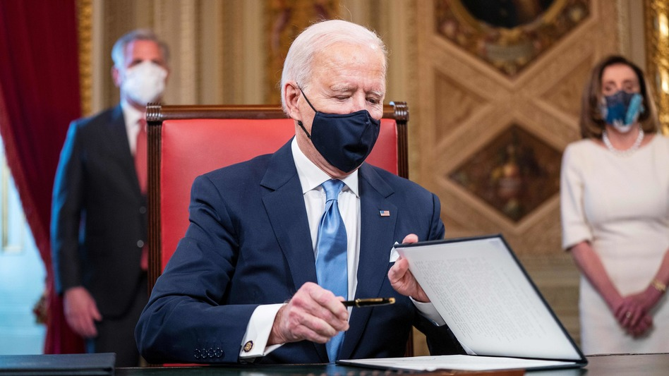 President Biden signs documents in the Presidents Room at the U.S. Capitol after taking the oath of office. (Jim Lo Scalzo/Pool/AFP via Getty Images)