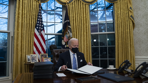 President Biden signs executive actions hours after his inauguration on Wednesday. He is expected to reverse several Trump-era policies.