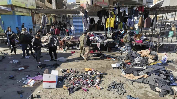People and security forces gather at the site of a deadly bomb attack Thursday in a Baghdad market. The rare suicide bombings killed and wounded dozens of civilians.