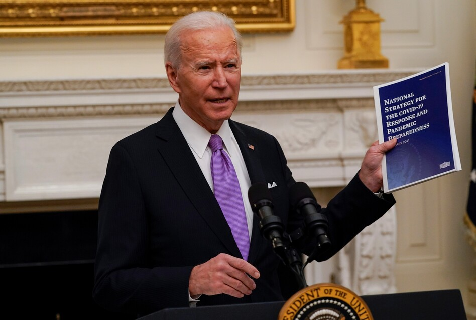 President Joe Biden holds a booklet as he speaks about the coronavirus in the State Dining Room of the White House, Thursday. (Alex Brandon/AP)