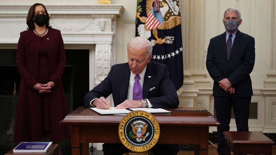 President Biden, joined by Vice President Harris and Dr. Anthony Fauci, signs executive actions as part of his administration's COVID-19 response on Thursday. (Mandel Ngan/AFP via Getty Images)