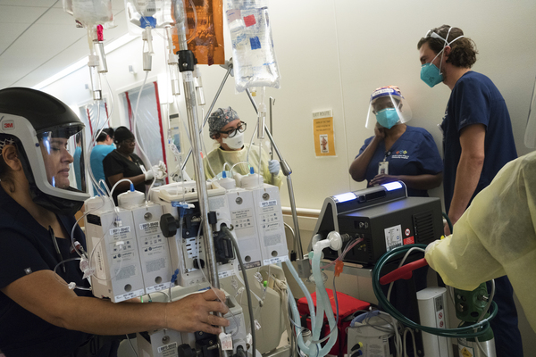 Maria Arechiga (center) helps move an intubated COVID-19 patient to a private room. The patient died later that day. Multiple COVID-19 deaths in one day are not rare at the hospital.
