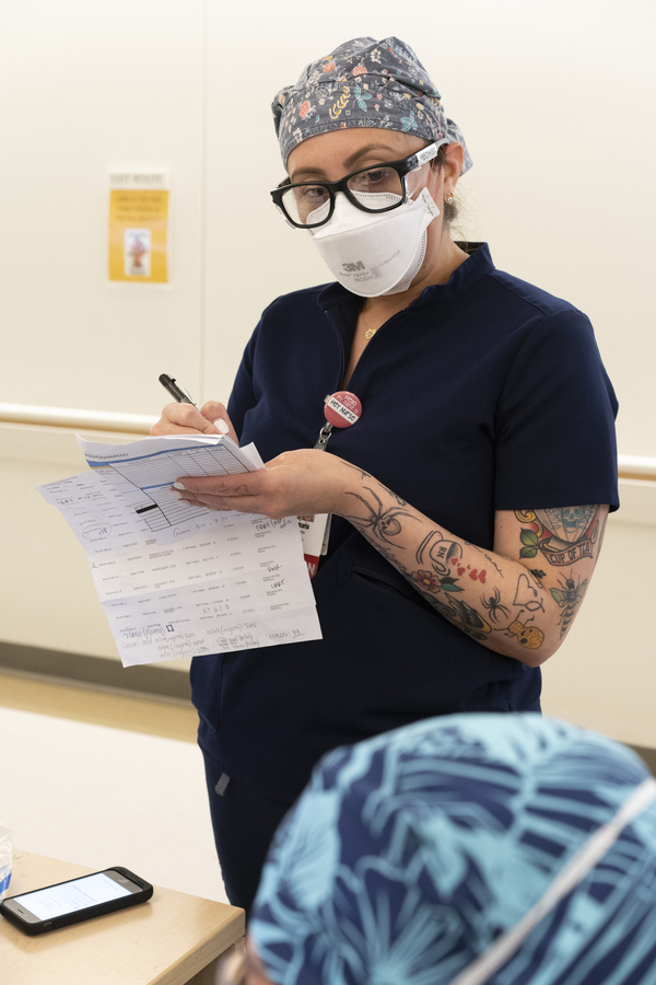 """Maria Arechiga takes notes on patients from a nurse who is leaving on lunch break. """"I feel like this time around, people are coming in sicker and dying quicker,"""" she says."""