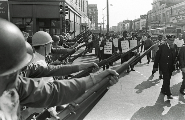 In February 1968, Black sanitation workers of Memphis began a strike to demand better working conditions and higher pay. On March 29, striking workers march past Tennessee National Guard troops with fixed bayonets during a 20-block march to City Hall.