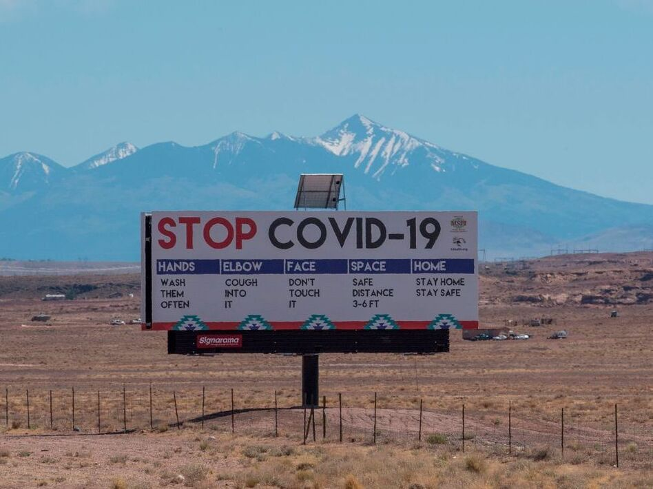 A sign warns against COVID-19 near the Navajo town of Tuba City, Ariz. As the pandemic rages across the U.S., mitigation measures continue to be critical to save lives. (Mark Ralston/AFP via Getty Images)