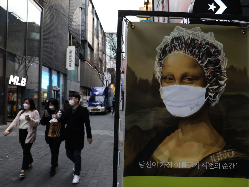 South Korea's KF94 mask does a good job concealing the <em>Mona Lisa</em>'s smile — but how effective is it at preventing coronavirus spread? Here, masked pedestrians stroll through a shopping district in Seoul. (Chung Sung-Jun/Getty Images)
