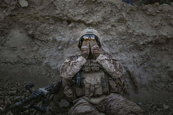 Marine Lance Cpl. Anthony Espinoza wipes sweat out of his eyes at the end of a patrol on a 100-degree day in Sangin, Helmand province, Afghanistan, May 2011.
