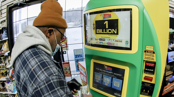 A patron, who did not want to give his name, uses the lottery ticket vending kiosk at a Smoker Friendly store to purchase tickets for the Mega Millions lottery drawing in Cranberry Township, Penn. The jackpot for the Mega Millions lottery game grew to $1 billion ahead of Friday night