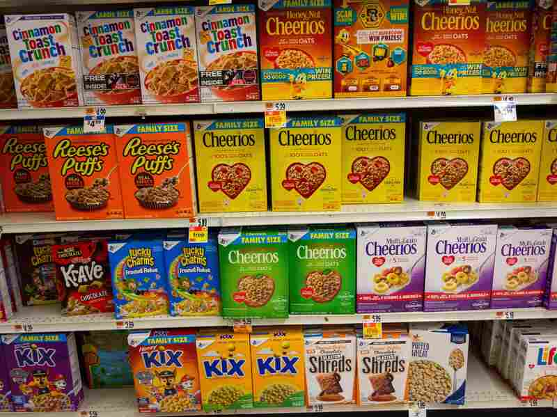 Several brands of cereal boxes fill the shelves at a grocery store.