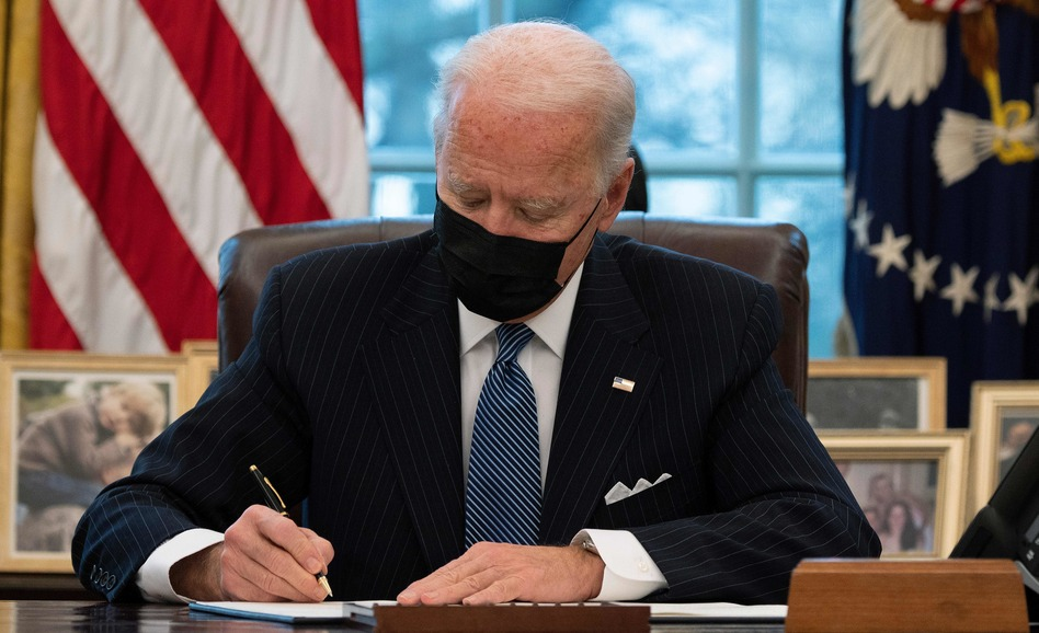 President Biden signs an executive order Monday reversing a Trump-era ban on transgender people serving in the military. (Jim Watson/AFP via Getty Images)