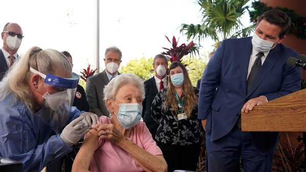 Florida Gov. Ron DeSantis watches as nurse Christine Philips (left) administers the Pfizer-BioNTech vaccine for COVID-19 to Vera Leip, 88, a resident of John Knox Village, Wednesday, Dec. 16, 2020, in Pompano Beach, Fla.