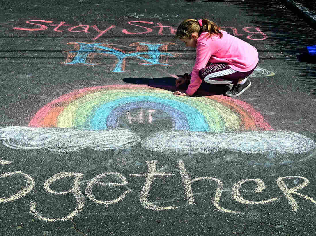 A girl makes chalk drawings on the driveway in West Islip, N.Y., in March 2020.