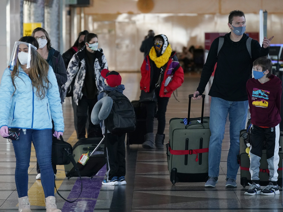 Masked travelers head through the main terminal of Denver International Airport on Dec. 31. Starting Feb. 1, travelers will be required to wear face masks on nearly all forms of public transportation. (David Zalubowski/AP)
