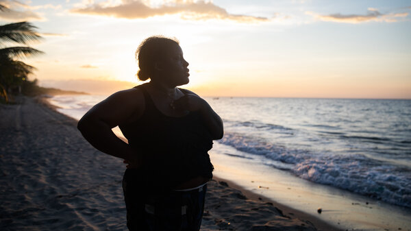 With the sun setting off the coast of northern Honduras, Ella Guity watches her daughters, Jirian and Eleny, swim in the warm Caribbean waters of the village of Rio Esteban, home to a group with African and indigenous roots known as the Garifuna. Ella had left years earlier for life in the big city, but the pandemic led her back home.