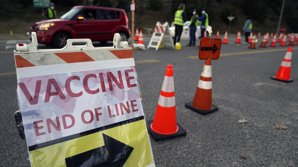 Drivers with an appointment enter a COVID-19 vaccination site set up in the parking lot of Dodger Stadium in Los Angeles on Saturday. One of the largest vaccination sites in the country was temporarily shut down because dozen of protesters blocked the entrance, stalling hundreds of motorists who had been waiting in line for hours.