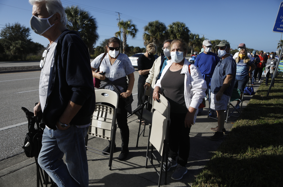 Long lines and computer isues are making it more difficult for some people to get the vaccine. These Floridians hope to snag one of 800 doses available at a vaccine site in Fort Myers. (Octavio Jones/Getty Images)