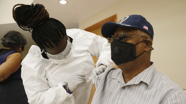 A health care worker administers the COVID-19 vaccine to a resident in Tampa, Fla., on Jan. 10. Seniors in Florida