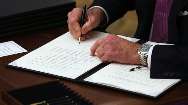 President Joe Biden signing an executive order in the State Dinning Room of the White House.