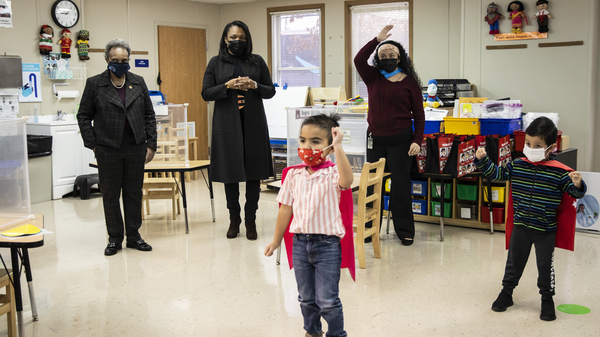 Mayor Lori Lightfoot, left, and Chicago Public Schools CEO Janice Jackson, second from left, visit a preschool classroom at Dawes Elementary School in Chicago on Jan. 11. The district wants more in-person classes to resume next week; the teachers union wants to continue teaching remotely.