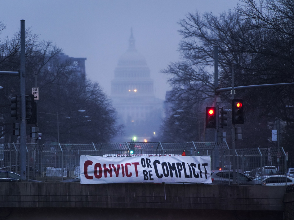 """A sign reading """"Convict or Be Complicit"""" hangs from a bridge on North Capitol Street in Washington, D.C., on the second day of former President Donald Trump's second impeachment trial. (Drew Angerer/Getty Images)"""