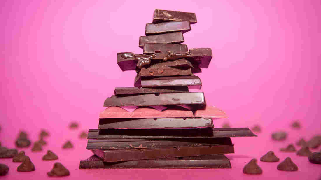 A tower made of stacked pieces of chocolate on a pink background with chocolate chips scattered around the base.