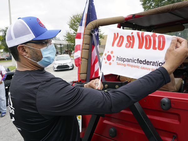 John Gimenez attaches a flag to his vehicle during an event hosted by the Hispanic Federation to encourage voting in the Latino community Sunday, Nov. 1, 2020, in Kissimmee, Fla. The Hispanic Federation is a non-partisan organization.
