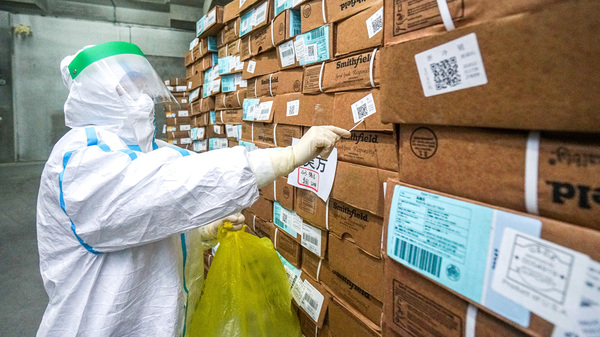 A health officer in a protective suit collects a sample from a package of imported frozen food for coronavirus rapid test at a wholesale market in China.