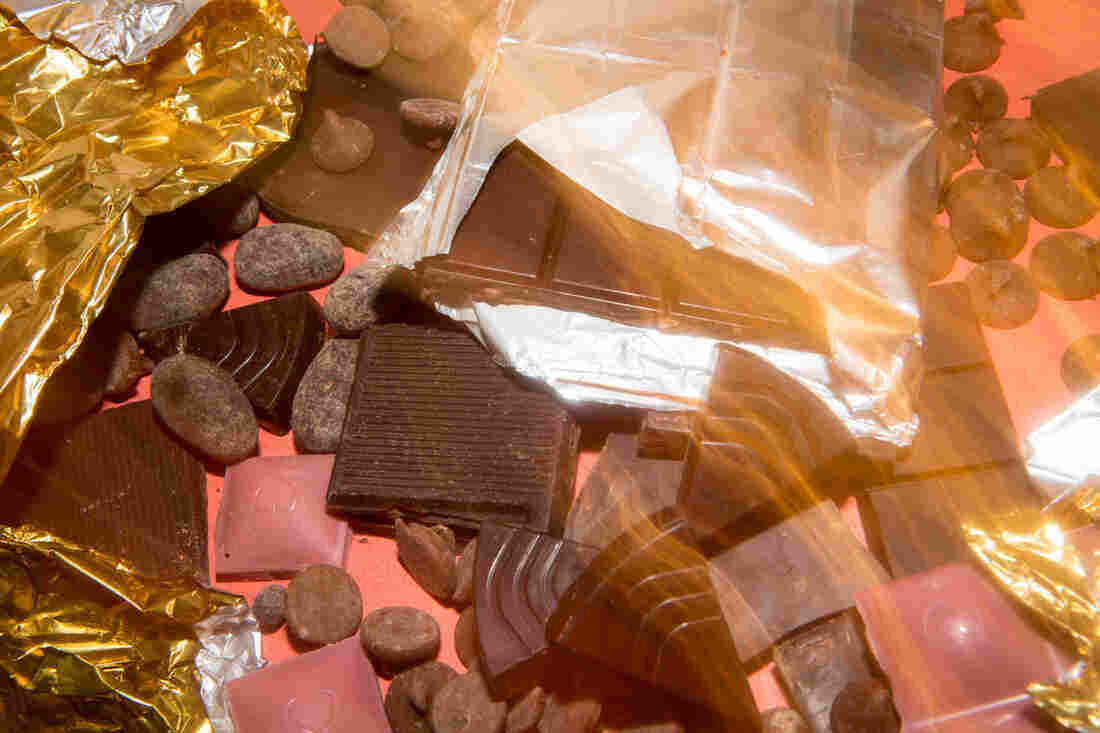 A long exposure photo of a pile of chocolate on a red background.