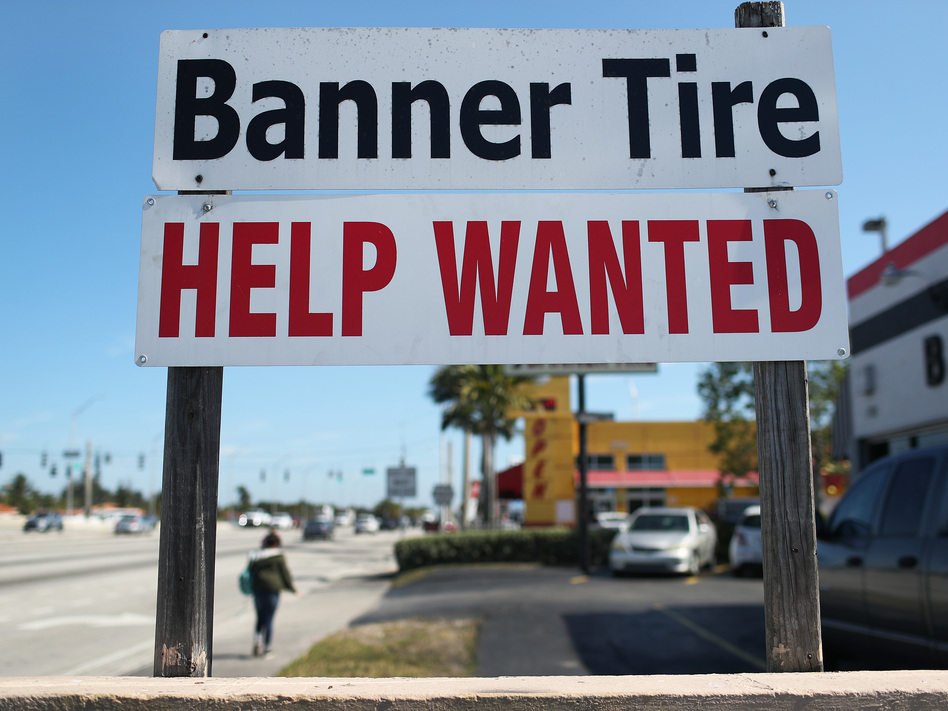 """A """"Help Wanted"""" sign is posted in front of a business on Feb. 4 in Miami. Although millions are unemployed, some businesses that require being on-site are struggling to find workers. (Joe Raedle/Getty Images)"""