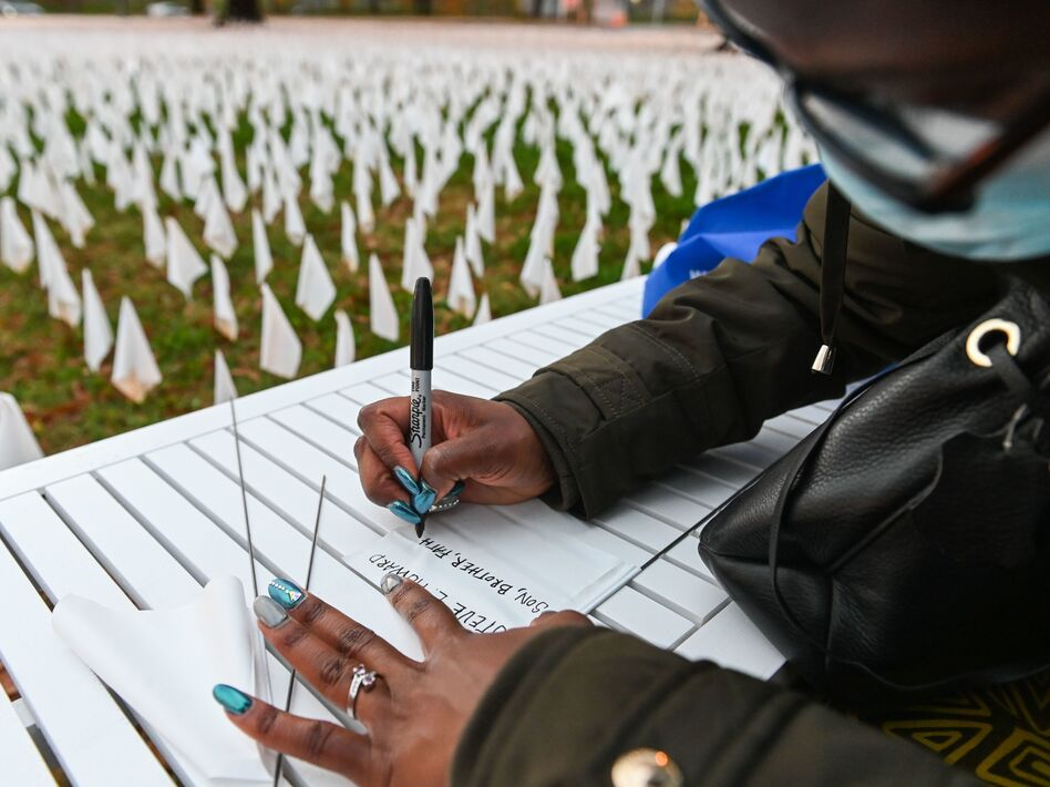 """Patrice Howard writes on white flags before planting them to remember her recently deceased father and close friends in November at """"IN AMERICA How Could This Happen...,"""" a public art installation in Washington, D.C. Led by artist Suzanne Firstenberg, volunteers planted white flags in a field to symbolize each life lost to COVID-19 in the U.S. (Roberto Schmidt/AFP via Getty Images)"""