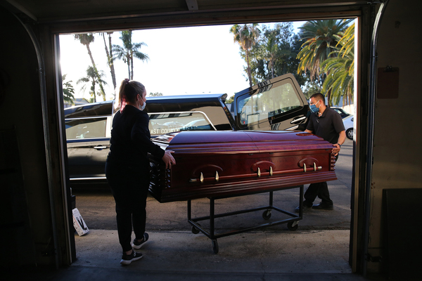 Embalmer and funeral director Kristy Oliver (left) and funeral attendant Sam Deras load the casket of a person who died after contracting COVID-19 into a hearse in El Cajon, Calif. People who work in hospitals and in funeral homes are witnesses to the loss than many Americans can avoid.