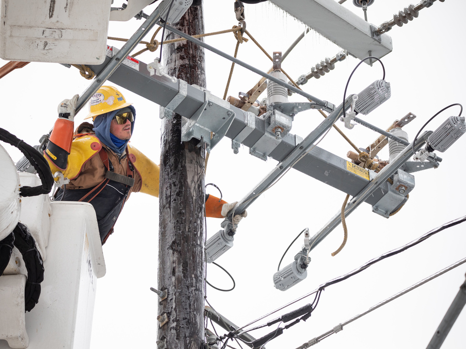 A worker repairs a power line in Austin, Texas, on Thursday. Although power was slowly being restored to much of the state, weather-related water issues persist. (Bloomberg via Getty Images)