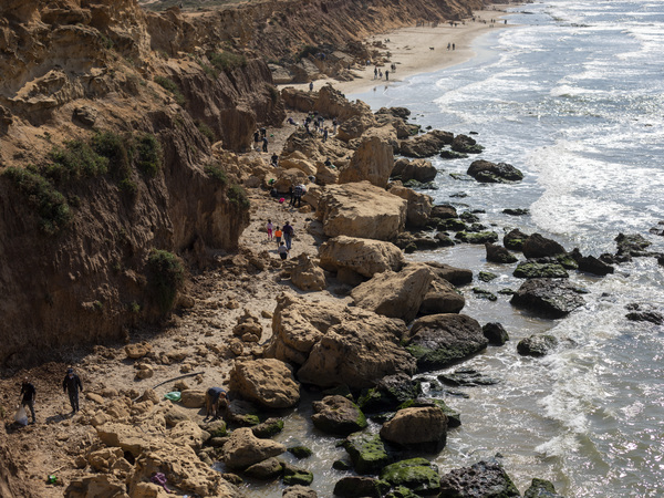 Volunteers at Gador nature reserve in Israel collect tar from an oil spill in the Mediterranean Sea on Feb. 20.