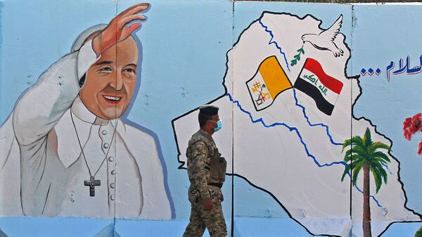 An Iraqi policeman walks by a mural depicting Pope Francis on the outer walls of Our Lady of Salvation Church in Baghdad on Monday. Pope Francis