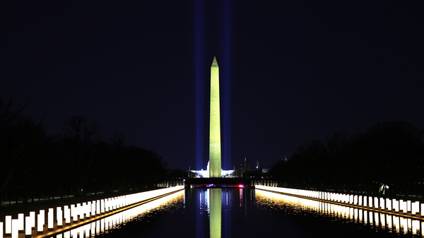 Columns along the sides of the Lincoln Memorial Reflecting Pool pay tribute to victims of COVID-19 at a Jan. 19 memorial. Just over a month later, a Monday evening ceremony will pay tribute to 500,000 Americans lives lost.