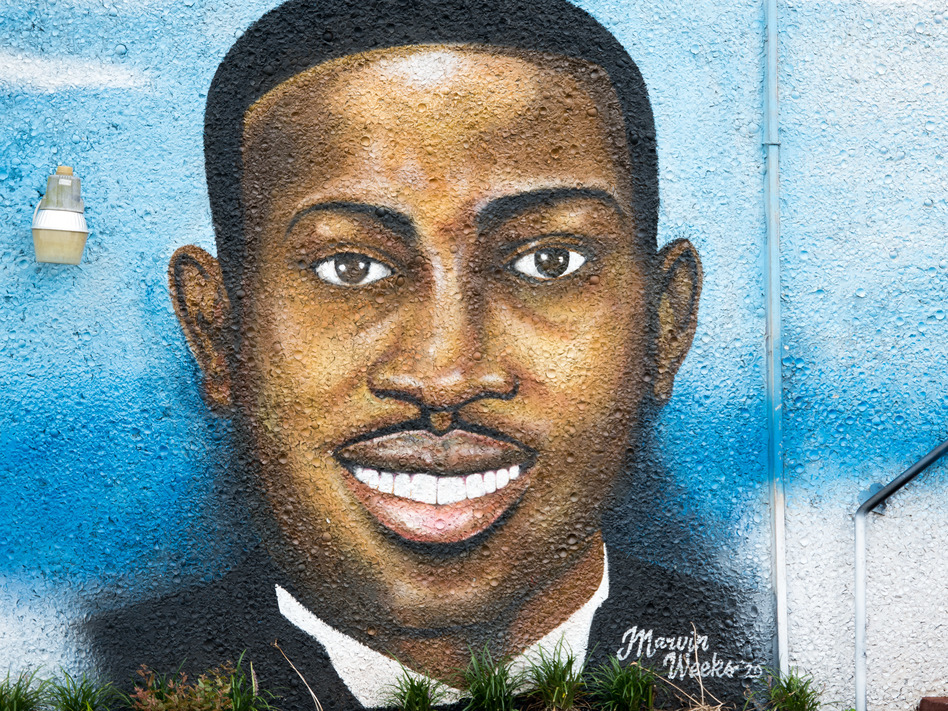 """A mural depicting Ahmaud Arbery in July 2020 in Brunswick, Ga. Gregory McMichael, Travis McMichael and William """"Roddie"""" Bryan are facing murder charges in connection with his death. (Sean Rayford/Getty Images)"""