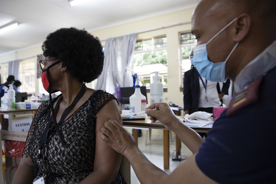 A health care worker looks away as she's immunized with Johnson & Johnson's COVID-19 vaccine at Klerksdorp Hospital in Klerksdorp, South Africa, on Feb. 18. (Phill Magakoe/AFP via Getty Images)