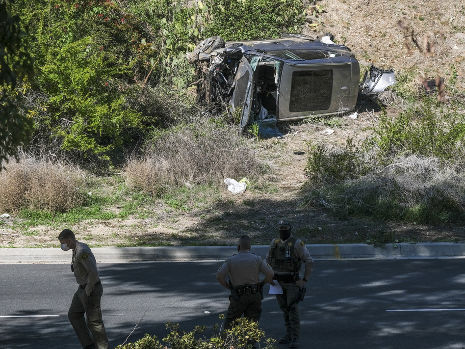 A vehicle rests on its side after a rollover accident involving golfer Tiger Woods along a road in the Rancho Palos Verdes section of Los Angeles County on Tuesday. Woods suffered leg injuries in the one-car accident and underwent surgery, authorities and his agent said. (Ringo H.W. Chiu/AP)