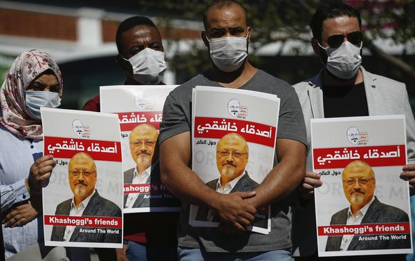 People hold posters of slain Saudi journalist Jamal Khashoggi, near Saudi Arabia's Consulate in Istanbul, marking the two-year anniversary of his death.
