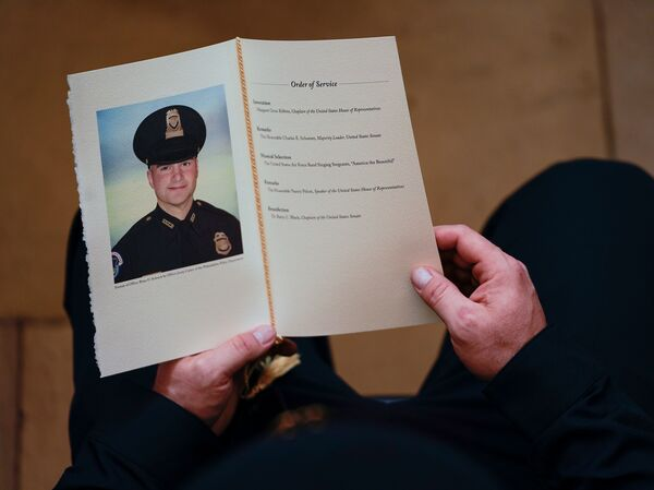 A Capitol Police officer holds a program as people pay their respects at the remains officer Brian Sicknick, who died after defending the Capitol against the Jan. 6 insurrection.