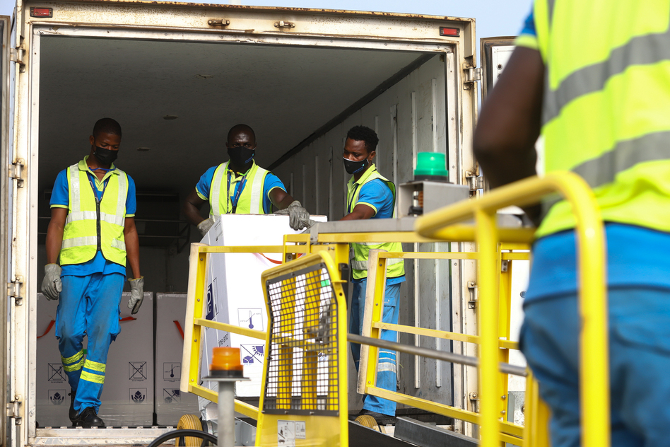 Ghana is the first country to receive a shipment of COVID-19 vaccines from the global COVAX program. Above: The vaccines are unloaded at the Kotoka International Airport in Accra on February 24. (Nipah Dennis/AFP via Getty Images)