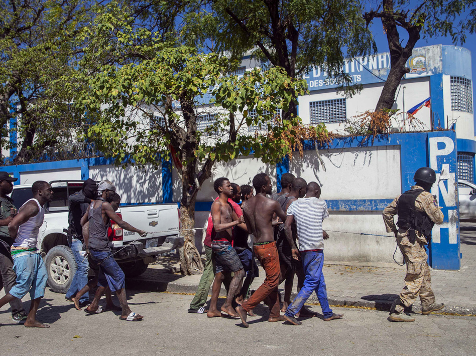 Police escort recaptured inmates back to the Croix-des-Bouquets Civil Prison after Thursday's outbreak in Port-au-Prince, Haiti. As of Friday night, authorities were still searching for more than 200 escapees. (Dieu Nalio Chery/AP)