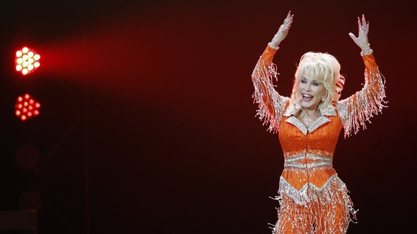 Dolly Parton, pictured performing in May 2014, shared a video of herself getting her first dose of the Moderna COVID-19 vaccine on Tuesday.