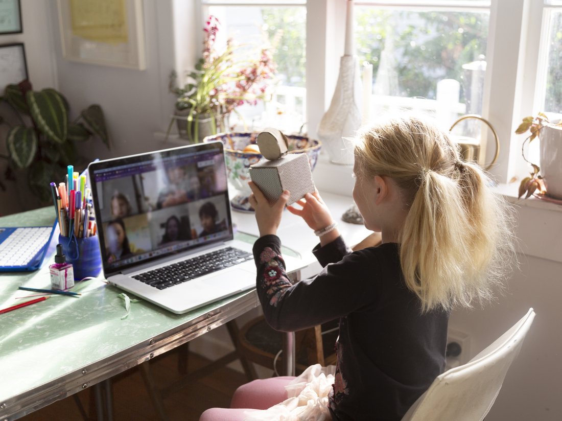 A girl shows her virtual classmates an art project she created in online school.