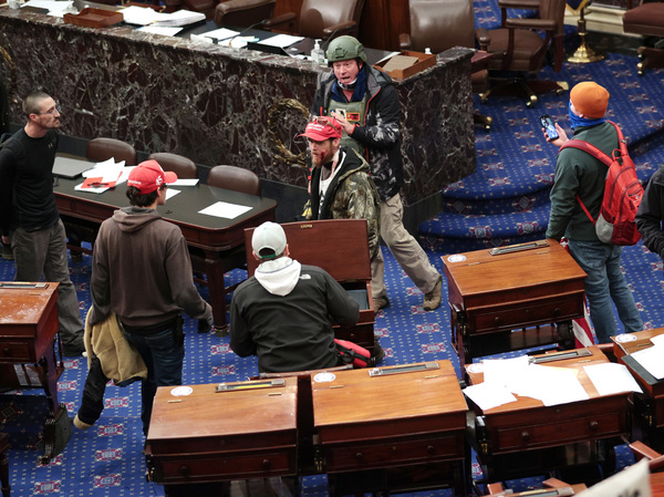 Bruno Cua is allegedly seen here with his back to the camera, holding a tan jacket. Prosecutors say he entered the Senate chamber of the U.S. Capitol on Jan. 6 with a handful of other rioters.