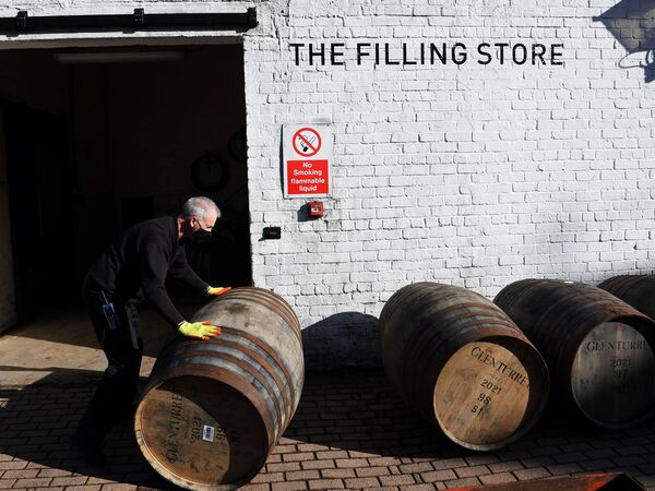 Scotch whisky producers are welcoming news of a breakthrough on tariffs, which came as the industry adjusted to both Brexit and then the COVID-19 pandemic. Here, an employee rolls a whisky barrel at the Glenturret Distillery in Crieff, central Scotland, last week.